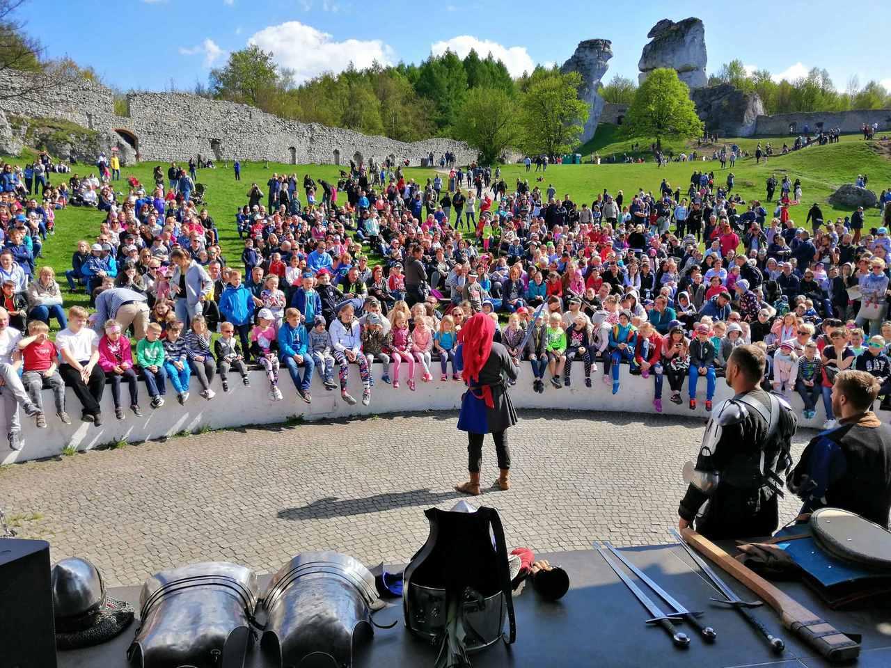 rycerz w stroju średniowiecznym podczas historycznej imprezy prezentuje się przed publicznością na scenie